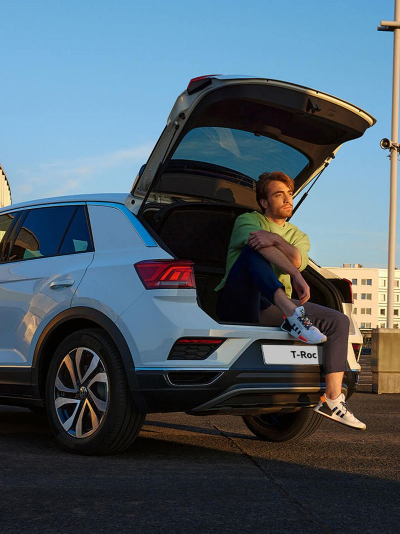 White VW T-Roc ACTIVE parked in an urban environment with an open luggage compartment.