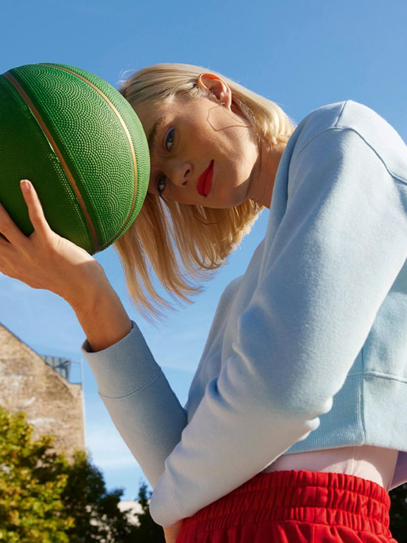 Woman holding a basketball in an urban environment with blue skies in the background.
