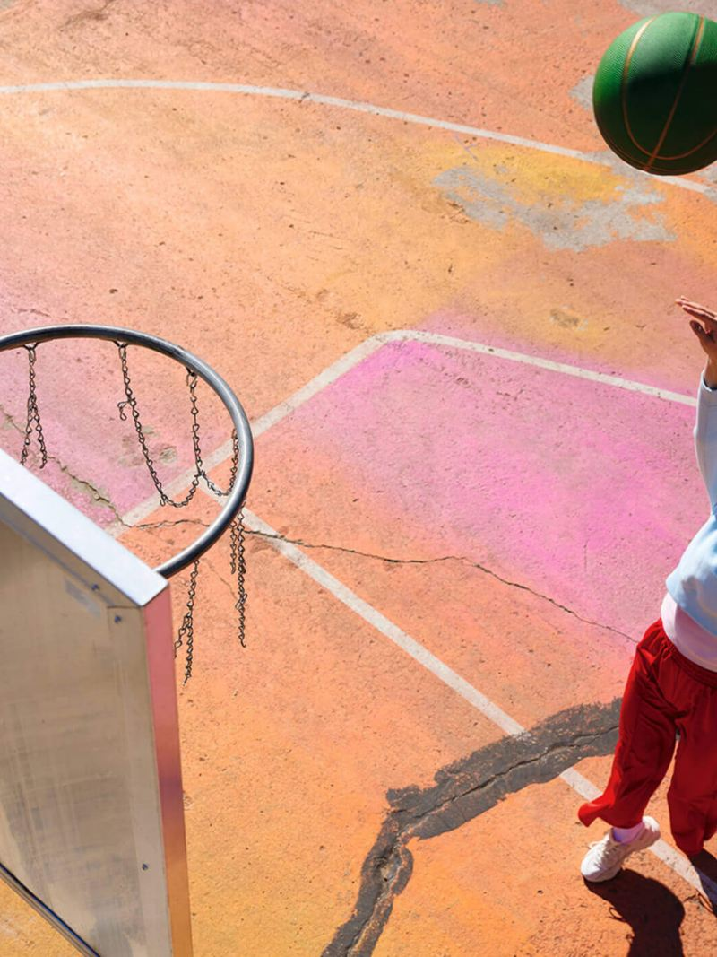 A woman in an urban setting throws a basketball towards a basket. Lifestyle.