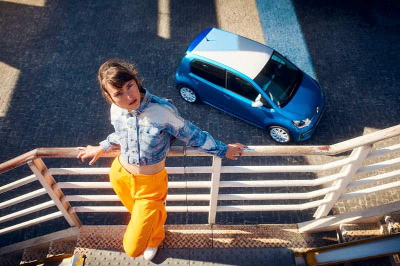 Aerial view of a parked new up! in blue with a lady standing on a balcony