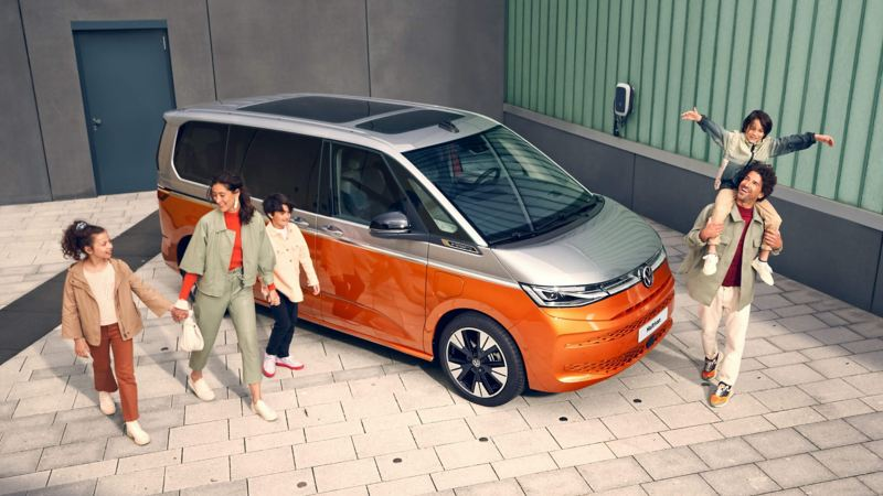 The new VW Multivan in an apartment complex environment with a family around it