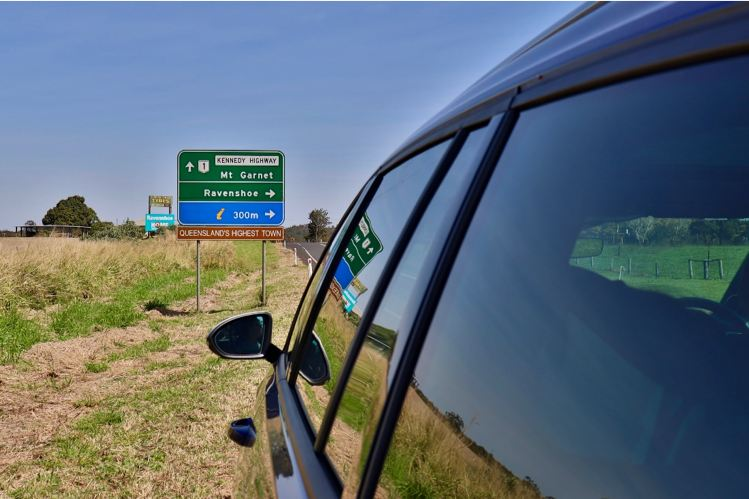 Car by highway sign