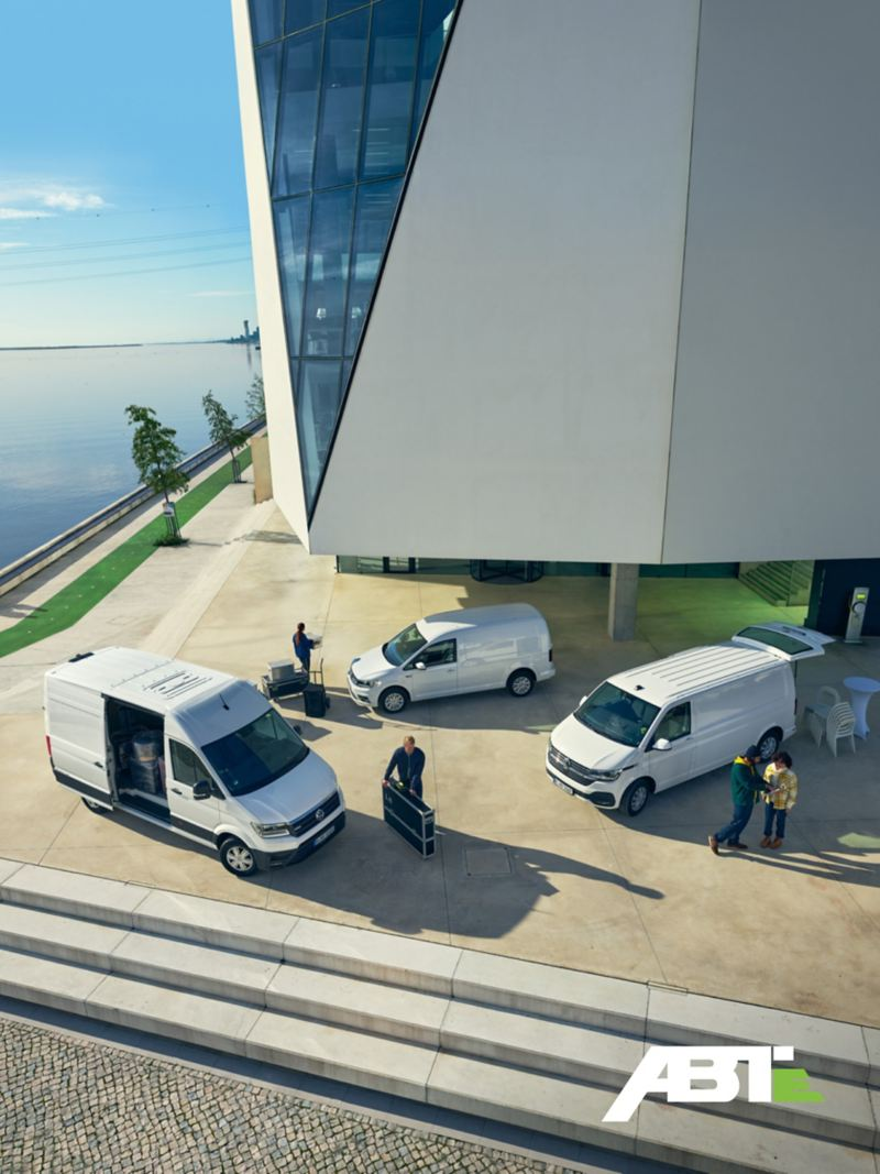 L'e-Crafter, l'ABT e-Transporter et l'ABT e-Caddy Volkswagen sont garés devant un complexe d'immeubles et en train d'être déchargés.