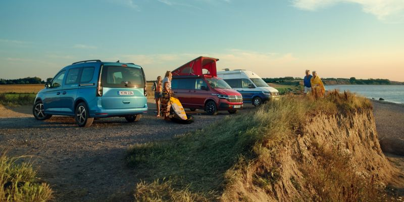 I tre modelli della Gamma California di Volkswagen parcheggiati davanti a una spiaggia.