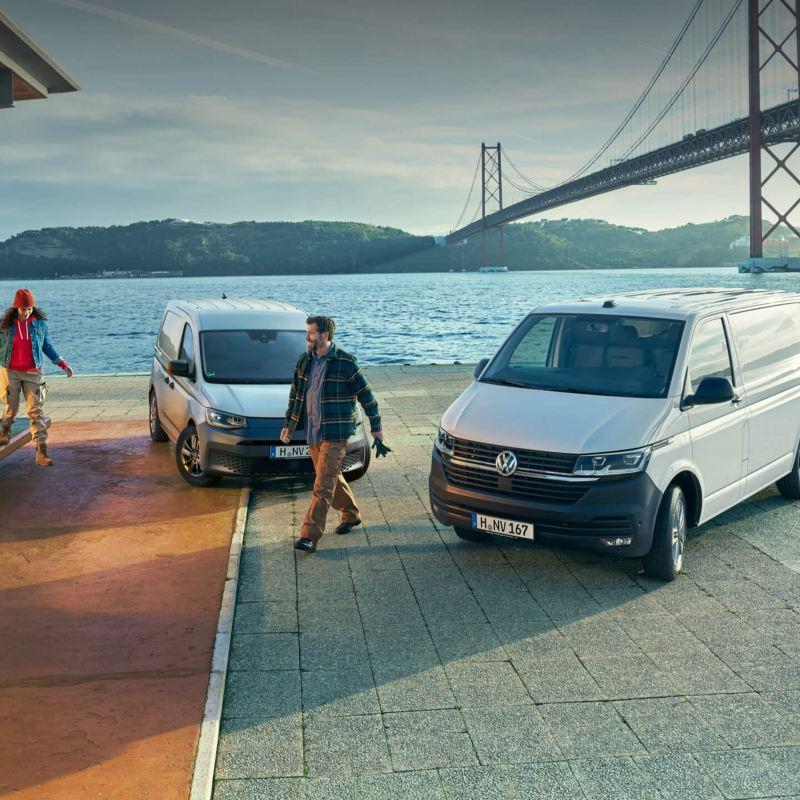 Ein VW Transporter 6.1 und ein Caddy Cargo vor einer Hafenkulisse.