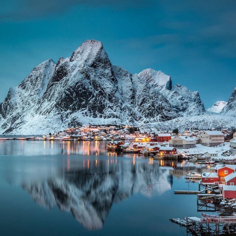 Ein norwegisches Dorf in der Dämmerung, direkt am Wasser, im Hintergrund Berge