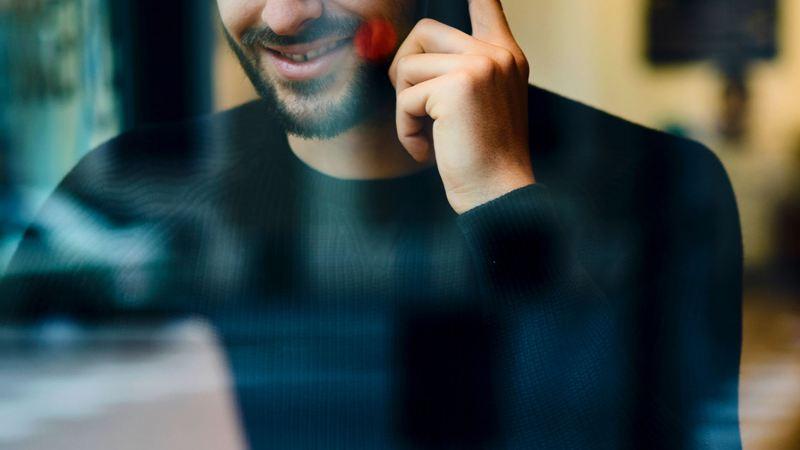 Un homme assit dans un café parlant au téléphone