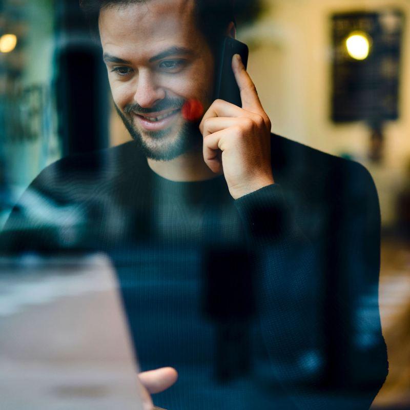 Un homme sur son téléphone portable devant un ordinateur