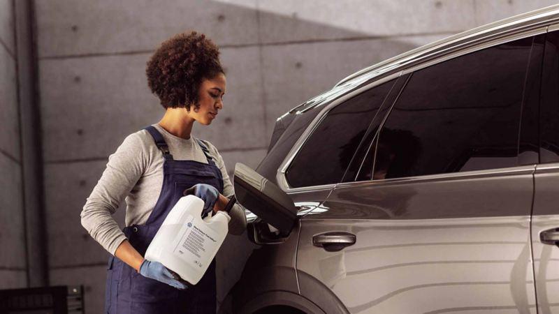 Un meccanico di Volkswagen Service rabbocca il liquido AdBlue di un'auto VW.