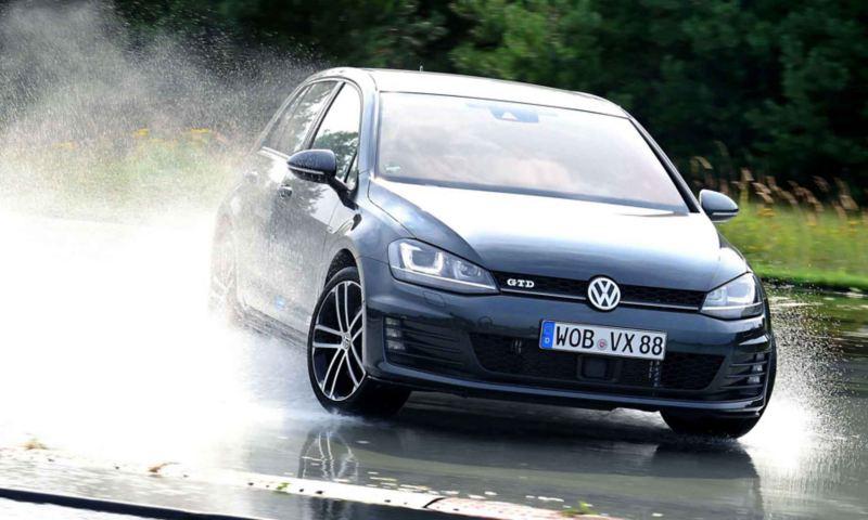Vista frontale di Volkswagen Polo GTD, attrezzata con pneumatici all-season, che attraversa una pozzanghera, sollevando uno spruzzo di acqua.