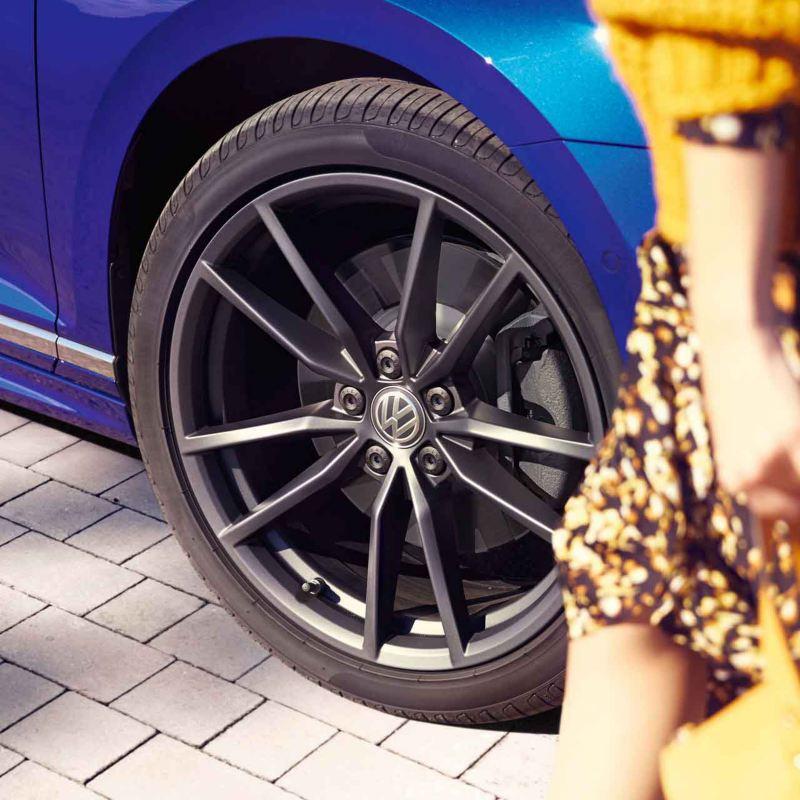 Dettaglio della ruota posteriore sinistra di un'auto Volkswagen.