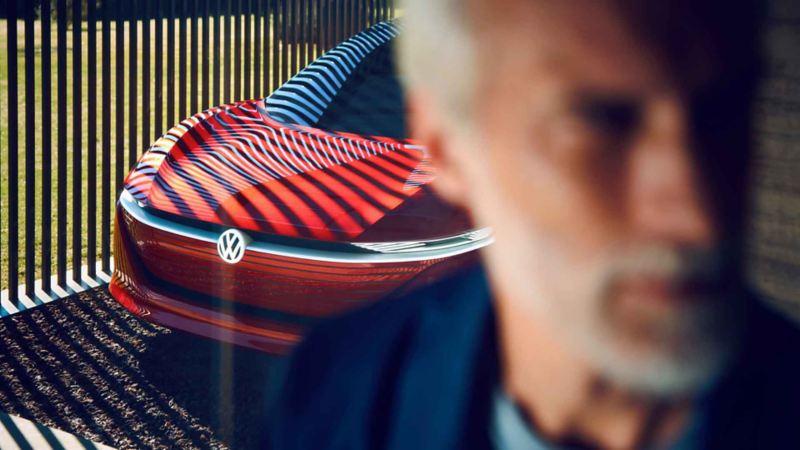 Uomo di spalle ad una Volkswagen ID. Vizzion rossa in un parcheggio coperto