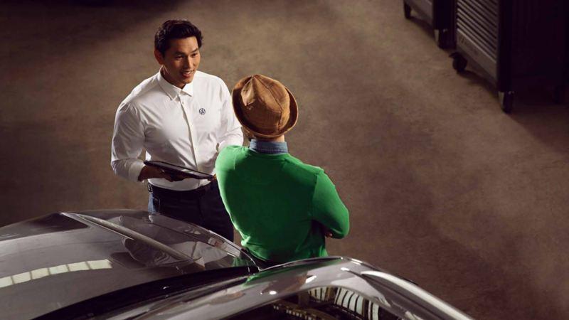 Un addetto Volkswagen parla con un cliente riguardo la manutenzione della sua auto