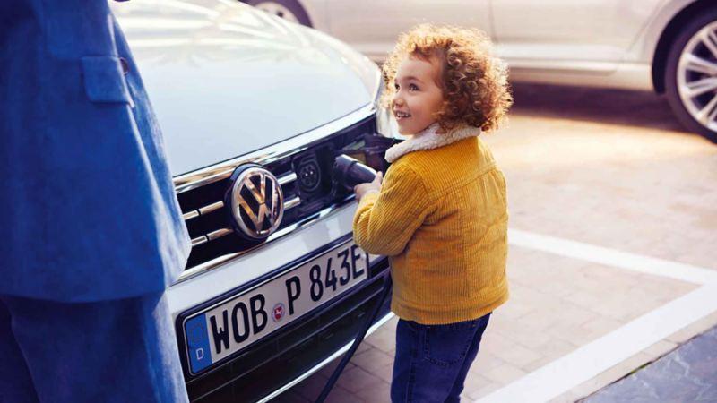 Una bambina inserisce il connettore per la ricarica nel cofano di un'auto ibrida plug-in Volkswagen