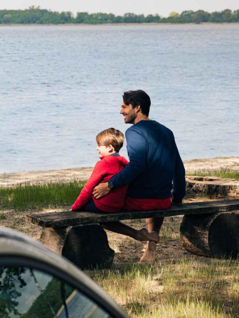 Un uomo e un bambino sono seduti su una panchina accanto a un lago. In primo piano, fuori fuoco, le barre portatutto originali Volkswagen montate su un'auto.
