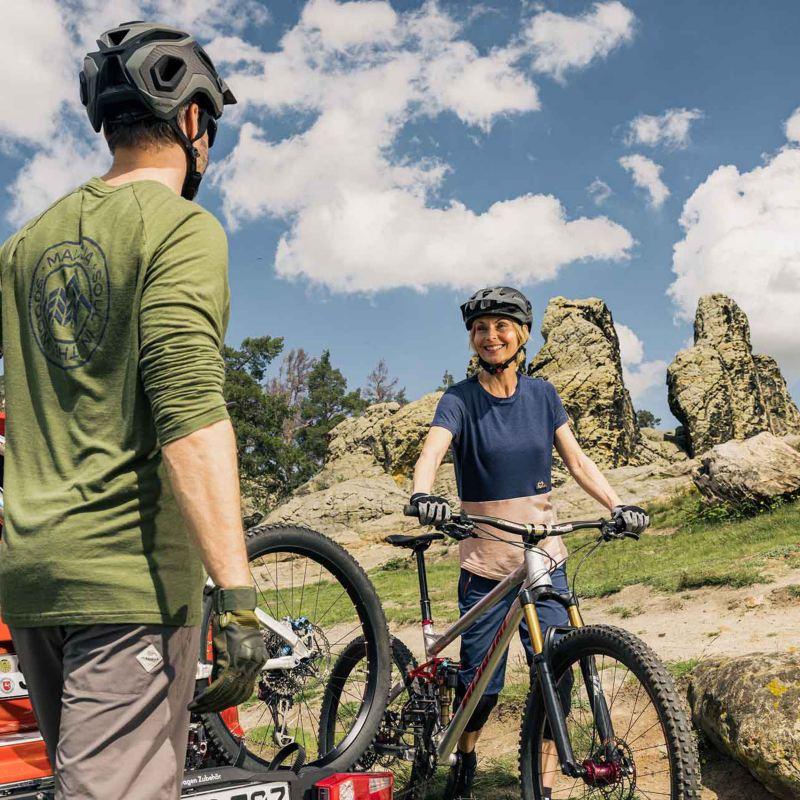 Due persone scaricano le loro biciclette da una Volkswagen Nuova Tiguan, vista posteriormente su una strada di montagna.