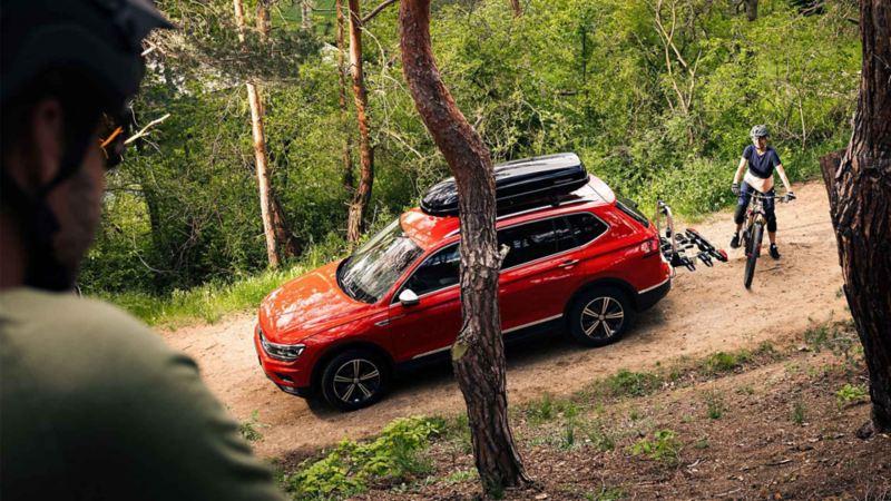 Un SUV Volkswagen percorre una strada sterrata di montagna con un box portatutto sul tetto.