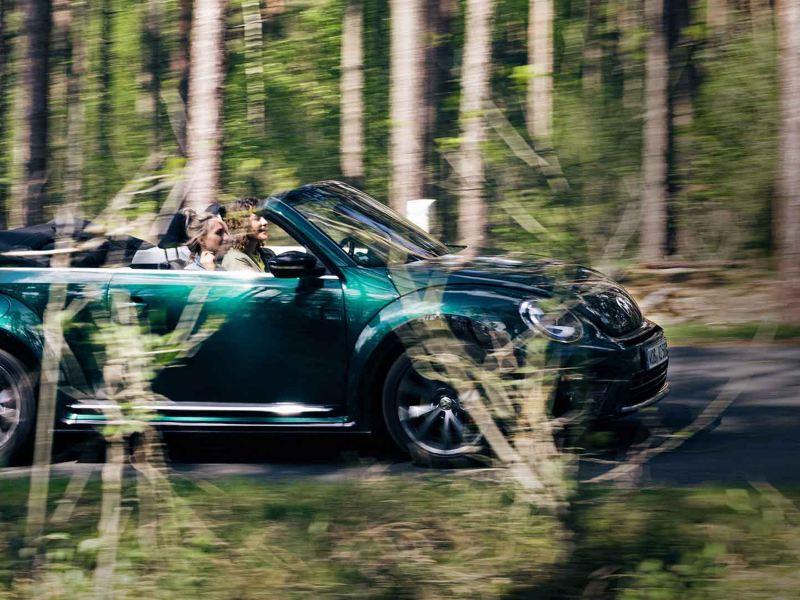 Due ragazze a bordo di una cabriolet Volkswagen guidano in mezzo a un bosco.