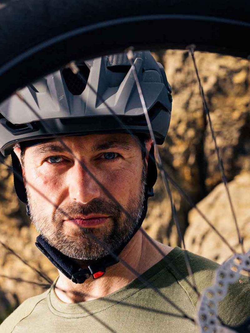 Un uomo con un caschetto visto attraverso i raggi della ruota della sua bicicletta.