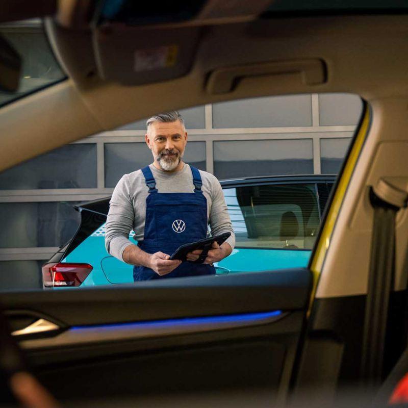Una donna siede nel posto di guida della sua auto; fuori dal finestrino si vede un tecnico Volkswagen Service.