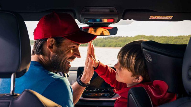 Un uomo e un bambino, seduti nei posti anteriori di un'auto Volkswagen, si battono il cinque.