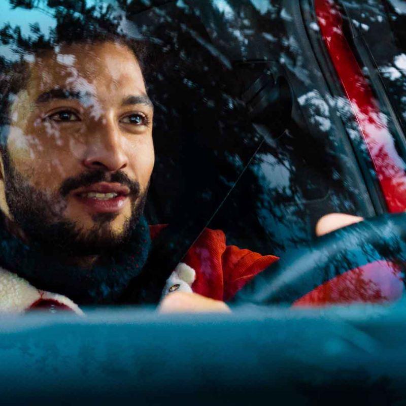 Vista attraverso il parabrezza frontale di un uomo che guida la sua auto Volkswagen.