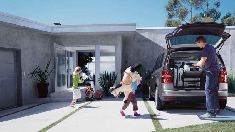 Una famiglia si prepara a partire per le vacanze a bordo di una monovolume Volkswagen
