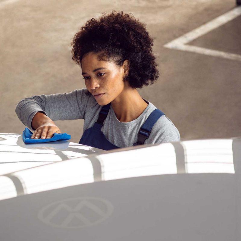 Una donna sta lucidando la carrozzeria di un veicolo con i prodotti Car Care di Volkswagen.