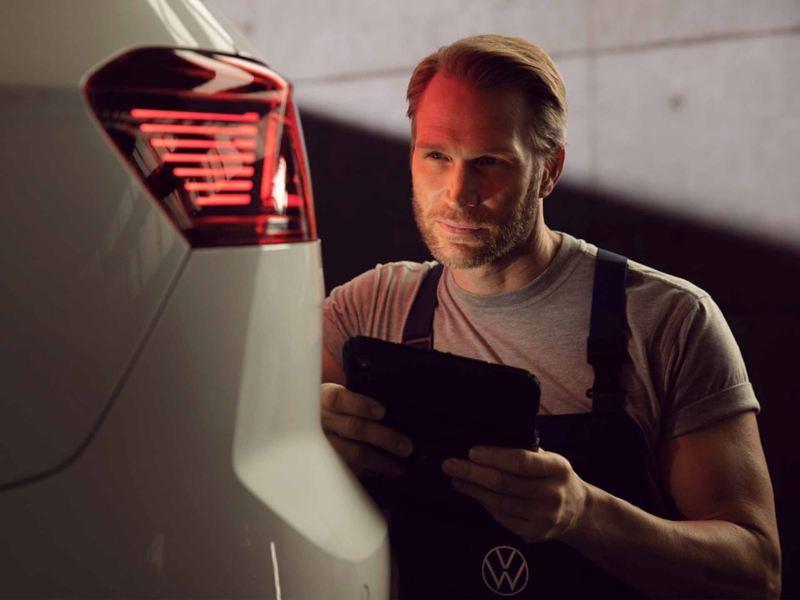 Un'auto elettrica Volkswagen all'interno di un'officina e-Service oggetto di ispezione da parte di un meccanico