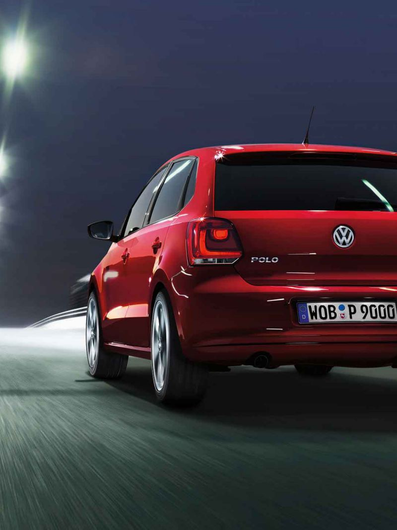 Posteriore Volkswagen Polo Highline 5 rossa mentre percorre una strada di notte.