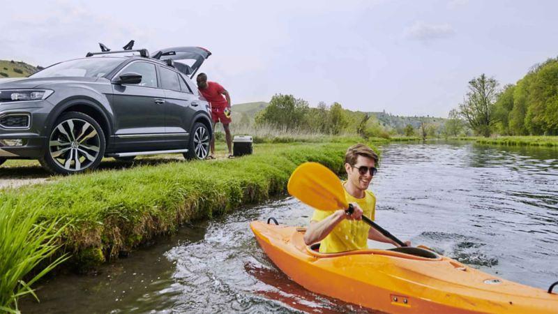 Il primo piano ragazzo che va su una canoa, dietro di lui un altro prende una borsa dal bagagliaio di una Volkswagen.