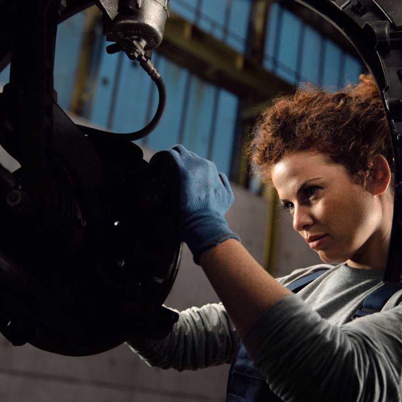 Un meccanico di Volkswagen Service esegue il cambio del liquido per i freni di un'auto VW.