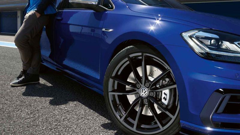 Vista frontale dal basso di Volkswagen Nuova Tiguan in allestimento R Line con dettaglio sul cerchio in lega anteriore destro.