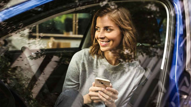 Una ragazza col cellulare in mano a bordo di una Volkswagen parcheggiata.