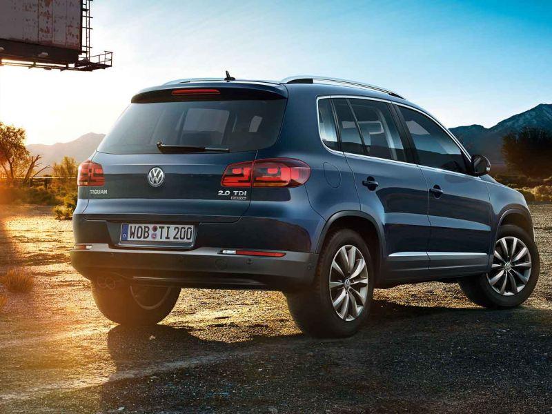 Vista 3/4 posteriore di Volkswagen Nuova Tiguan su una strada di montagna al tramonto.