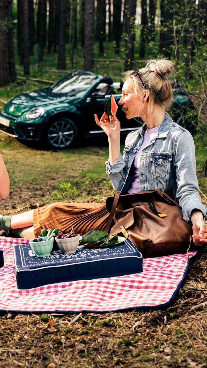 Due ragazze fanno un picnic su un prato. Sullo sfondo una cabriolet Volkswagen vista lateralmente.