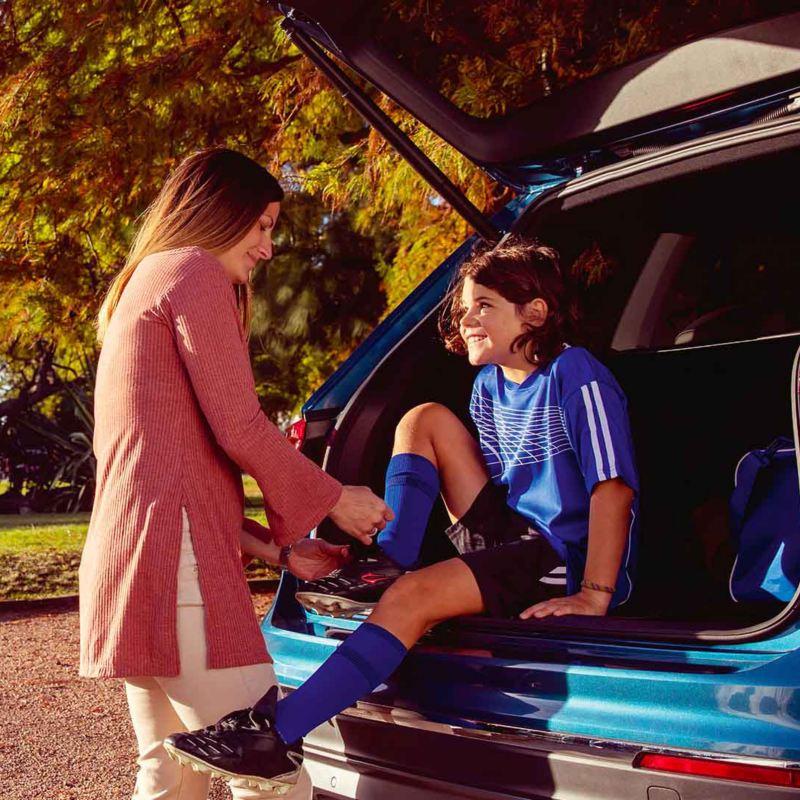 Mamma allaccia le scarpe da calcio al figlio seduto nel bagagliaio di un'auto Volkswagen