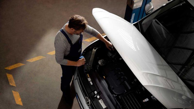 Un meccanico di Volkswagen Service ispeziona il motore di un'auto VW col cofano aperto.