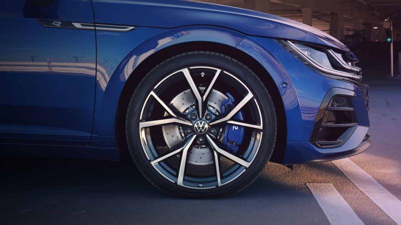 Dettaglio della ruota anteriore destra di un'auto Volkswagen con  pinza per freni e cerchi in lega sportivi.