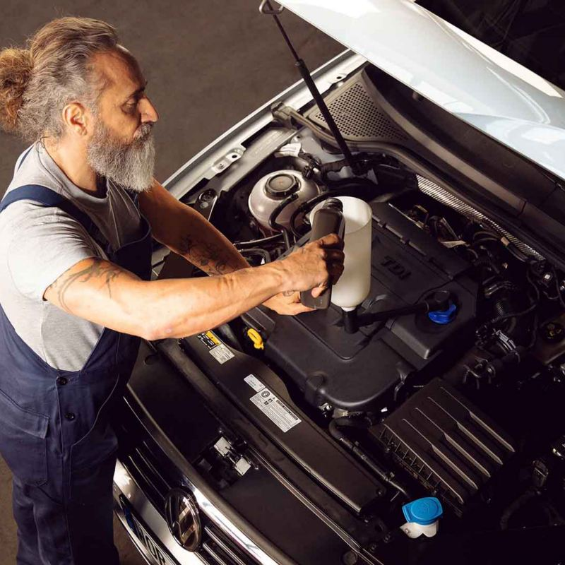 Un meccanico di Volkswagen Service controlla il livello del liquido refrigerante di un'auto VW.