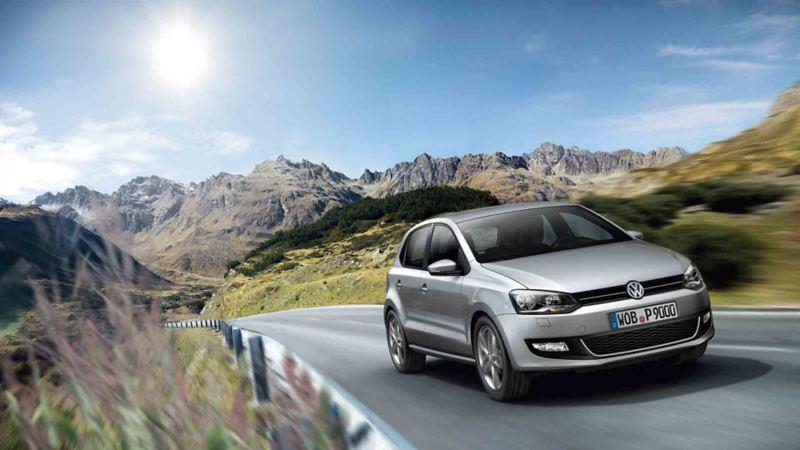 Vista 3/4 frontale di Volkswagen Polo che percorre una strada di montagna.