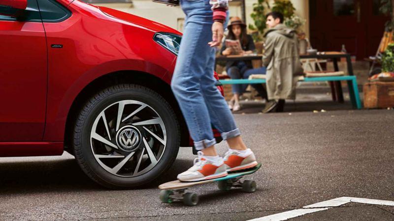 Un ragazzo con il suo skateboard mentre passa vicino a una Volkswagen. Dettaglio sul cecio in lega anteriore destro.