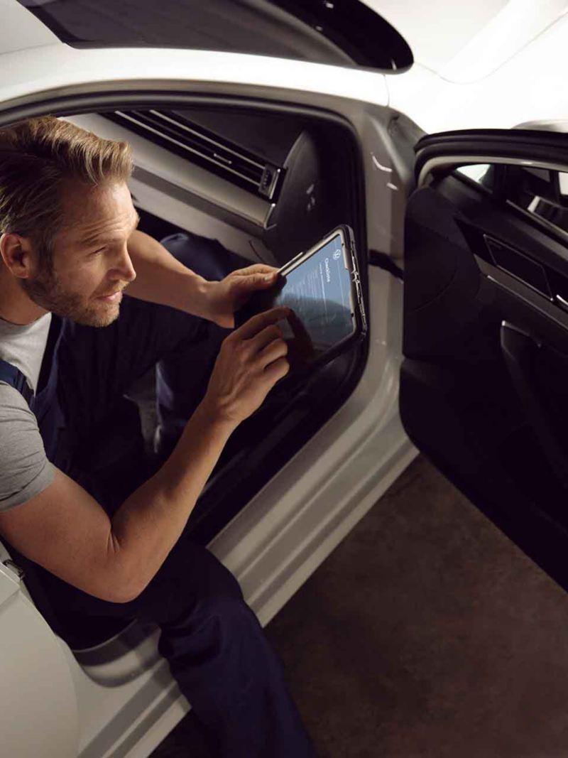 Un meccanico di un centro Volkswagen Service esegue un'ispezione all'interno di un'auto