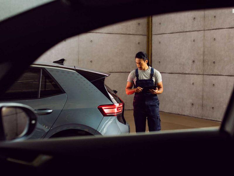 Meccanico Volkswagen in officina che effettua un controllo su un'auto con l'aiuto di un tablet