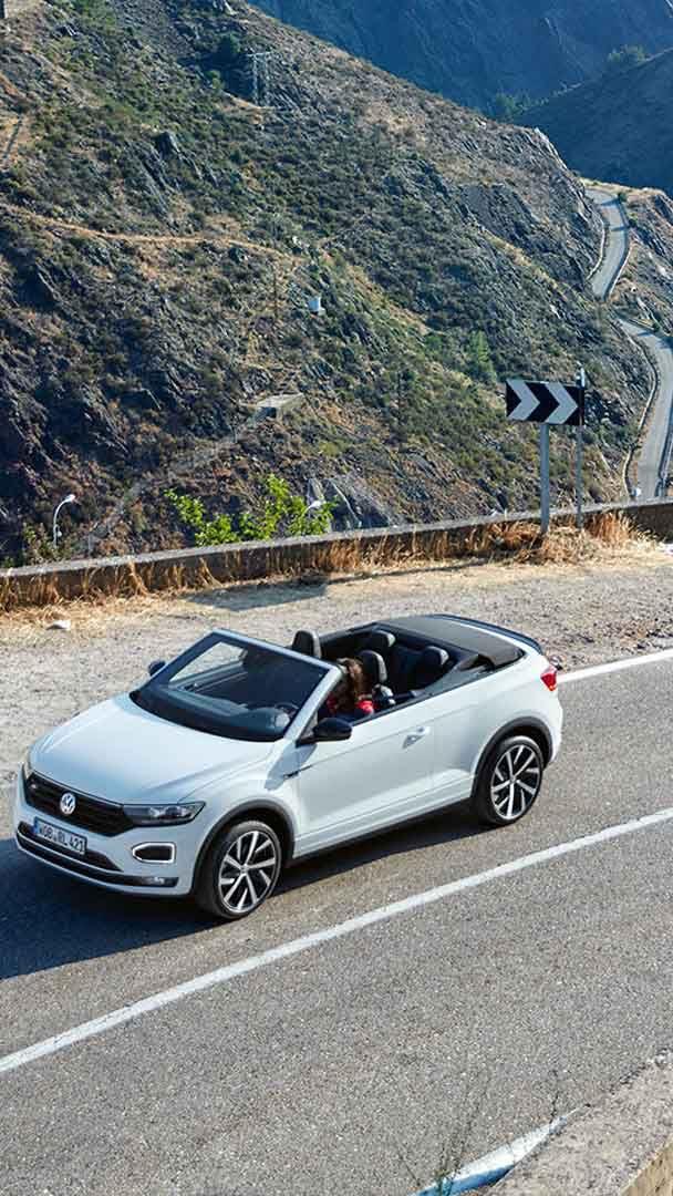 Una Volkswagen T-Roc Cabriolet percorre una strada di montagna