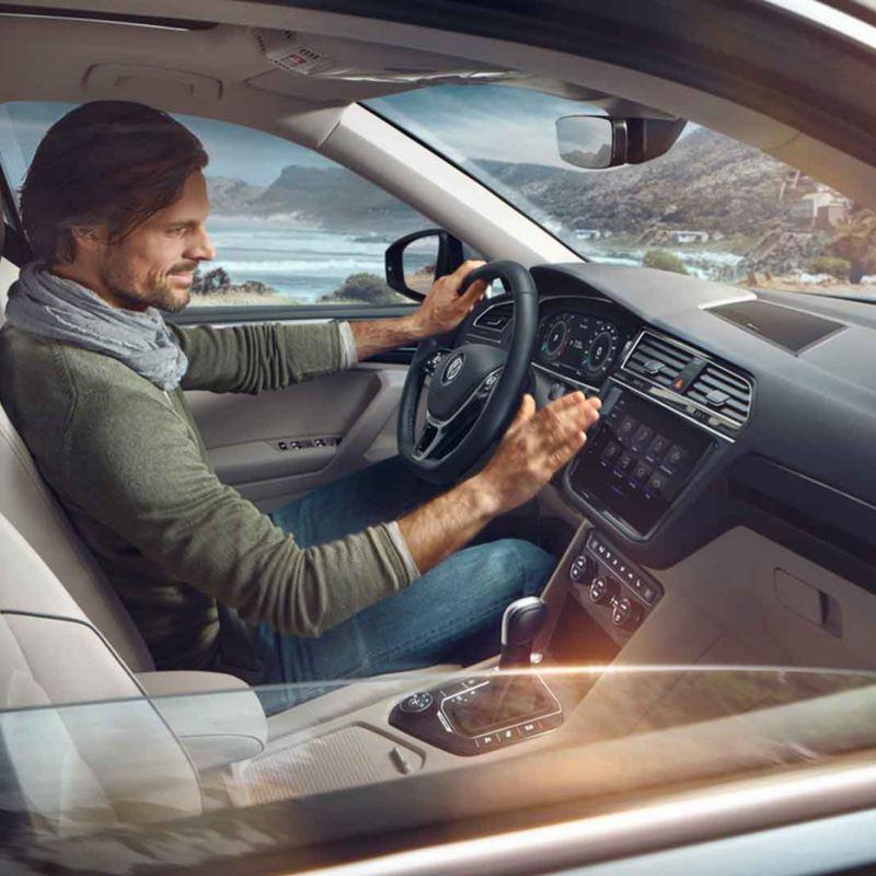 Uomo alla guida di una Volkswagen Tiguan Allspace vista attraverso il finestrino anteriore destro abbassato.