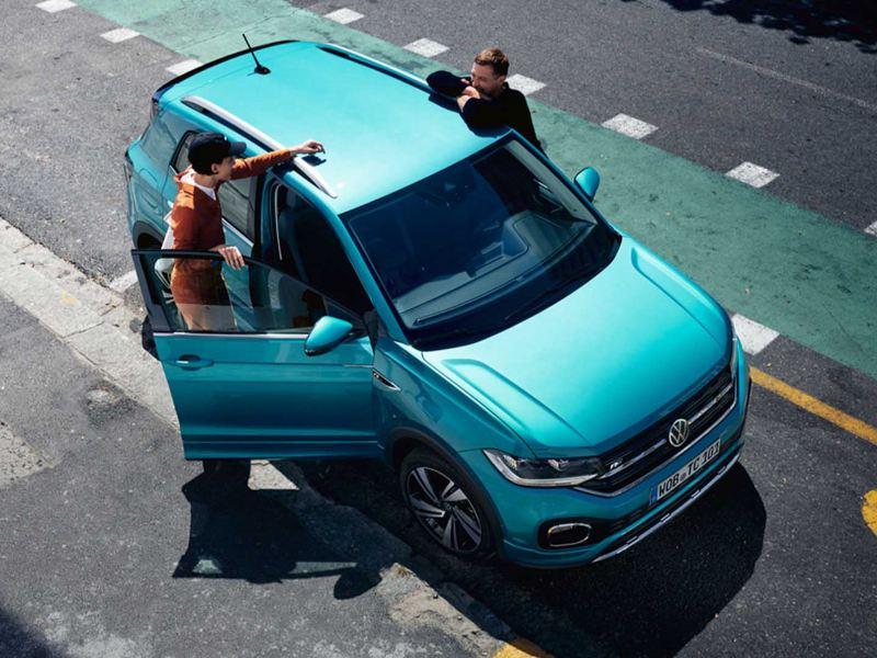 Due persone appoggiate alla loro auto Volkswagen.