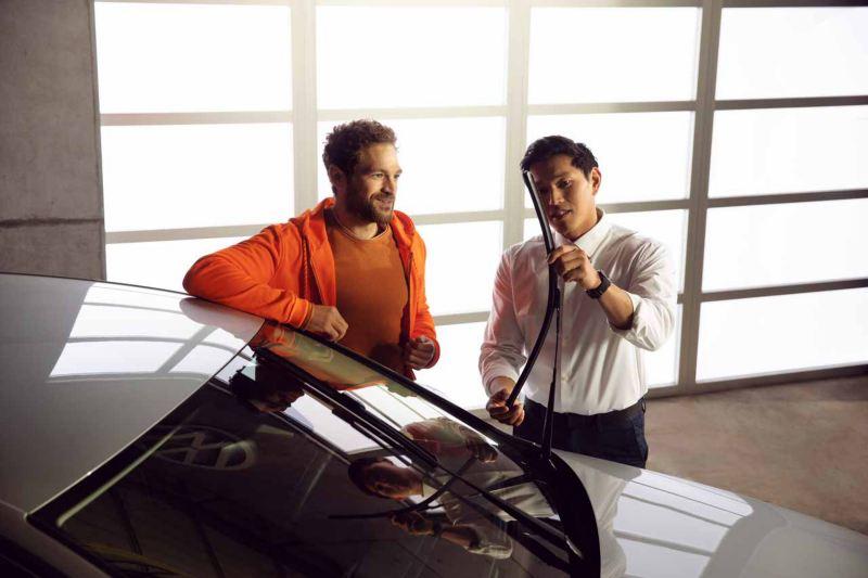 Un impiegato Volkswagen mostra a un cliente i tergicristalli di un'auto Volkswagen.