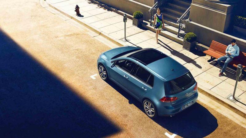 Vista 3/4 posteriore dall'alto di Volkswagen Golf parcheggiata a bordo strada.