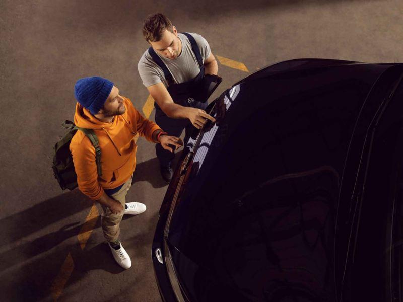 Un addetto Volkswagen Service controlla la vernice di un'auto